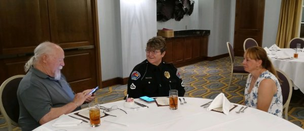 Officer Groggin, her husband and Col Woddard wait to be served lunch.jpeg